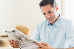 Smiling casual man reading newspaper in kitchen Stock Photo