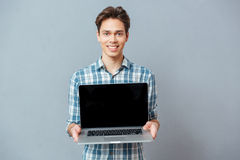 Smiling casual man showing blank laptop computer Stock Photo