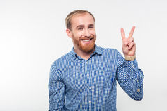 Smiling casual man showing victory sign. Portrait of a smiling casual man showing victory sign on a white background Royalty Free Stock Photos