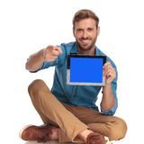 Smiling casual man sitiing with tablet and pointing finger. On white background Royalty Free Stock Images