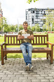 Smiling casual man with tablet computer sitting on the bench. Royalty Free Stock Image
