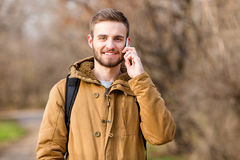 Smiling casual man talking on the phone outdoors Stock Image