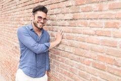 Smiling casual man touching brick wall Stock Image