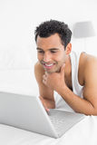 Smiling casual man using laptop in bed Stock Image