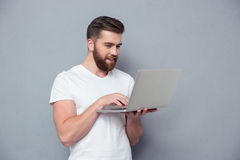 Smiling casual man using laptop computer Royalty Free Stock Images