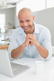 Smiling casual man using laptop at home Royalty Free Stock Images