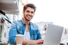 Smiling casual man using laptop while sitting at cafe outdoors Royalty Free Stock Photography
