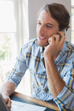 Smiling casual man using laptop and talking on smartphone Stock Photos