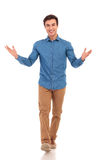 Smiling casual man welcoming you and walking forward. On white studio background Royalty Free Stock Photography