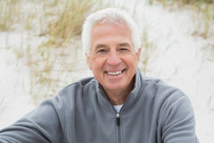 Smiling casual senior man relaxing at beach Stock Images