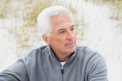 Smiling casual senior man relaxing at beach Stock Photo