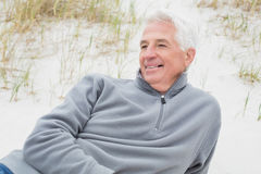 Smiling casual senior man relaxing at beach Royalty Free Stock Photo