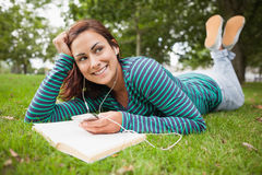 Smiling casual student lying on grass listening to music Stock Image