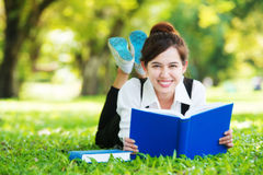 Smiling casual student lying on grass reading book Stock Photo