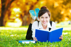 Smiling casual student lying on grass reading book Royalty Free Stock Photography