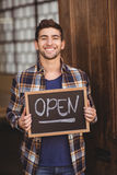 Smiling casual waiter showing chalkboard with open sign Royalty Free Stock Image