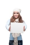 Smiling casual winter girl holding sign Stock Image