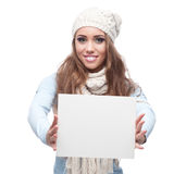 Smiling casual winter girl holding sign Stock Photo