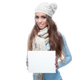 Smiling casual winter girl holding sign Royalty Free Stock Photography