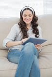 Smiling casual woman on cosy couch using tablet pc Royalty Free Stock Photo
