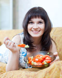Smiling casual woman eats tomatoes salad Royalty Free Stock Images