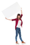 Smiling Casual Woman Is Holding  Blank Poster Over Her Head Royalty Free Stock Photography