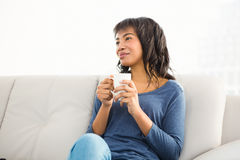 Smiling casual woman holding coffee and looking otherwise Stock Images