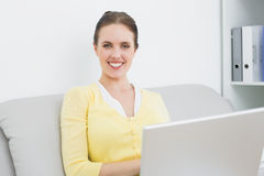 Smiling casual woman with laptop sitting at home. Portrait of a smiling casual young woman with laptop sitting on sofa at home Stock Photos