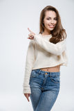 Smiling casual woman pointing finger away Stock Photography