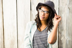 Smiling casual woman posing with glasses and hat. Against wooden plank Stock Photos