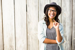 Smiling casual woman posing with glasses and hat. Against wooden plank Stock Photo