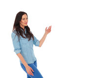 Smiling casual woman presenting something to side. On white studio background Stock Image
