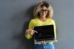 Smiling casual woman showing laptop screen over gray background. Looking at camera. Smiling casual woman showing laptop screen over gray background. Looking at royalty free stock photo