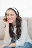 Smiling casual woman sitting on a cosy couch having a phone call Royalty Free Stock Image