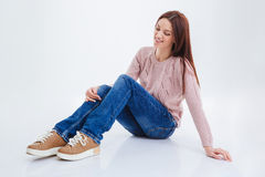 Smiling casual woman sitting on the floor. Isolated on a white background Royalty Free Stock Photos