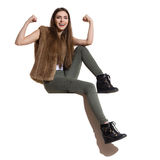 Smiling Casual Woman Is Sitting On A Top And Flexing Muscles Stock Photo