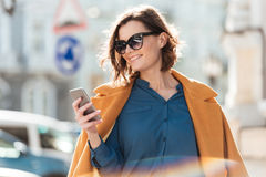 Smiling casual woman in sunglasses looking at mobile phone. While standing on a city street Royalty Free Stock Photos