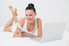 Smiling casual woman using cellphone and laptop in bed Royalty Free Stock Photos