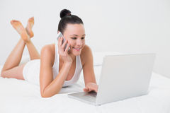 Smiling casual woman using cellphone and laptop Royalty Free Stock Photography