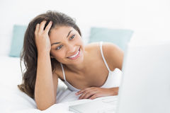 Smiling casual woman using laptop in bed. Smiling casual young woman using laptop in bed at home Royalty Free Stock Images