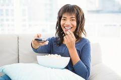 Smiling casual woman watching tv with popcorn Royalty Free Stock Photography