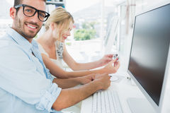 Smiling casual young couple working on computer Royalty Free Stock Images