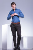 Smiling casual young man buttoning his shirt Royalty Free Stock Images