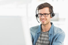Smiling casual young man with headset using computer Stock Images