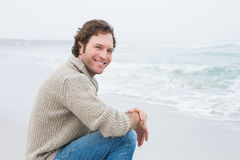 Smiling casual young man relaxing at beach Stock Image