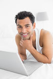 Smiling casual young man using laptop in bed Royalty Free Stock Image