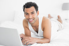 Smiling casual young man using laptop in bed Stock Images