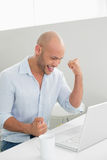 Smiling casual young man using laptop at home Royalty Free Stock Photos