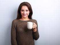 Smiling casual young woman with cup of tea looking happy Stock Photo