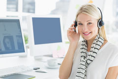Smiling casual young woman with headset in office Royalty Free Stock Images